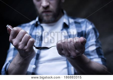 Looking at drugs with desire . Mad bearded skilled junky standing in the dark lighted room while preparing cocaine dose and holding spoon and syringe