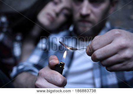 Severe physical and mental suffering. Skilled concentrated young junkies siting in the darkness while heating drug dose and using spoon and lighter