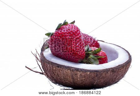 Strawberries in a coconat bowl. Beautiful juicy and bright strawberryes in a bowl of half coconut on white background.  Healthy concept