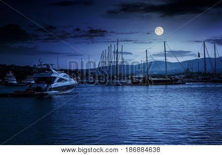 yacht at the pier of the old city at night in full moon light