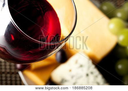 Wine cheese glass of wine red wine focus on foreground close up wine glass