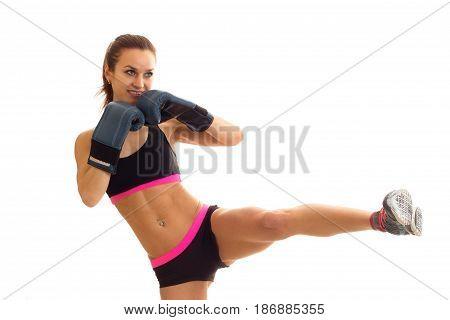 young Super athletic girl in boxing gloves and lifted her top leg up isolated on white background