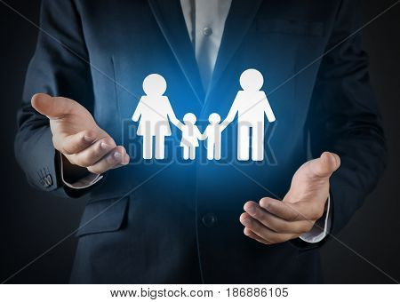 Insurance concept. Businessman holding symbol of family in hands, closeup