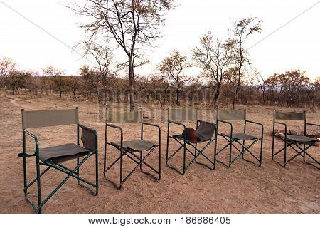 picture of safari chairs set up facing the sunset, South Africa.