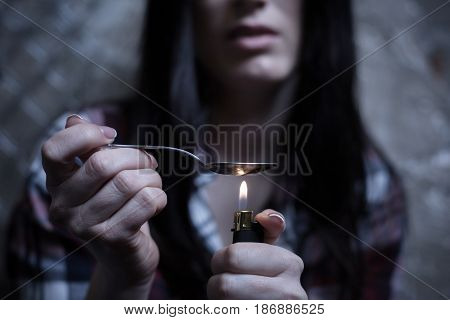 Nobody supports me. Upset involved drug user sitting in the darkness and heating cocaine dose while using spoon and cigarette lighter