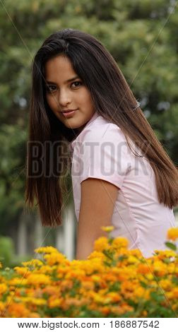 A Teen Girl Sitting Among Many Flowers