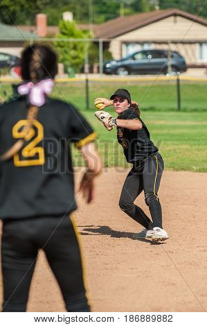 Teenage softball infielder with her eyes on the target.