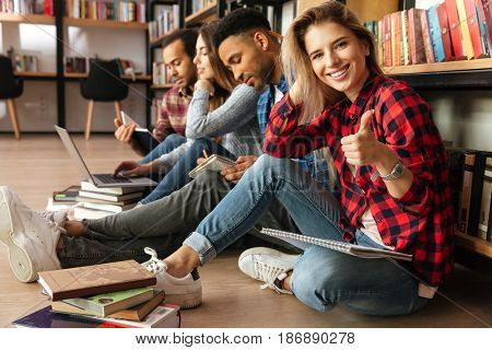 Picture of young students sitting in library on floor using laptop computer and reading book. Woman looking at camera showing thumbs up.