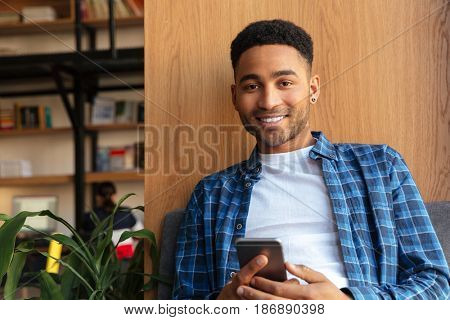 Picture of young happy african man student sitting in library chatting by mobile phone. Looking at camera.
