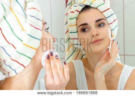 beautiful girl with towel on the hair stands before the mirror and rubs your face with a cotton disk close-up