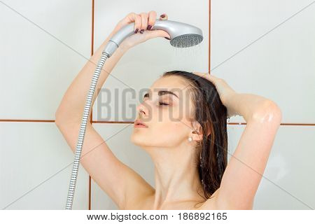beautiful young girl stands under the shower closing her eyes and washes her head close-up