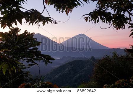 Evening sunset nature of Batur volcano and Agung mountain surrounded by tropical nature in Kintamani region of Bali island. Indonesia landscape at dusk with soft pinf light, outdoor nature photography