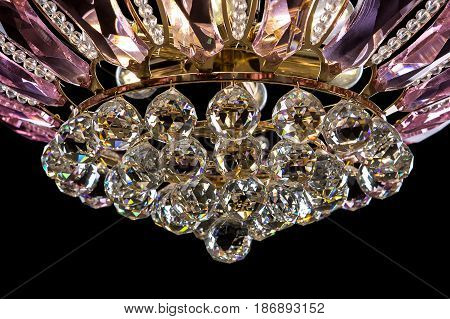 Contemporary gold chandelier isolated on black background. Crystal chandelier decorated pink crystals. close-up
