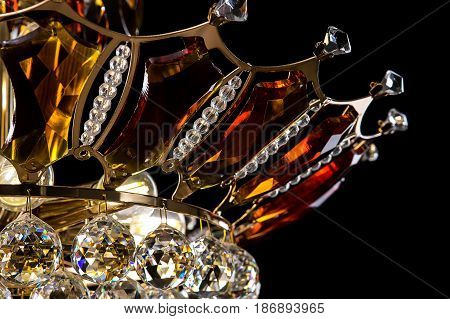 Contemporary gold chandelier isolated on black background. Crystal chandelier decorated amber crystals. close-up