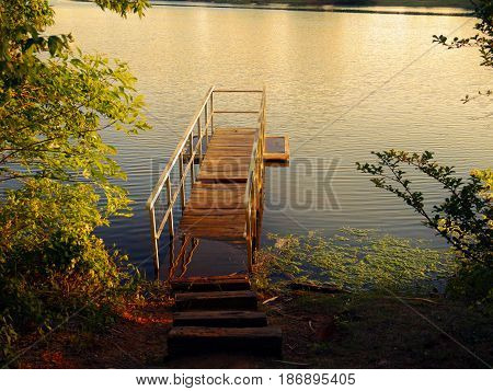 Wooden dock in the water A wooden dock partly submerged in the water of a lake