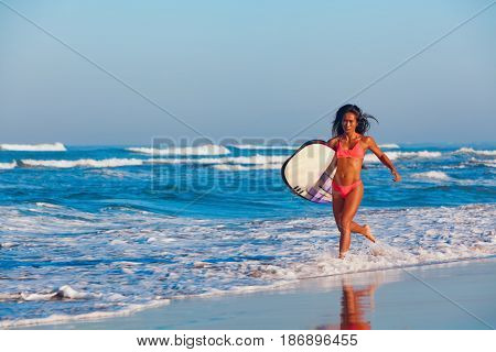 Girl in bikini with surf board has fun. Woman surfer run into water jump with splashes through ocean wave. People in water sport adventure camp beach extreme activity on summer beach family vacation