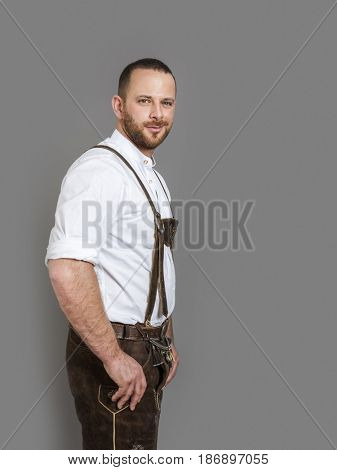 An image of a man in bavarian traditional outfit for Oktoberfest isolated on grey