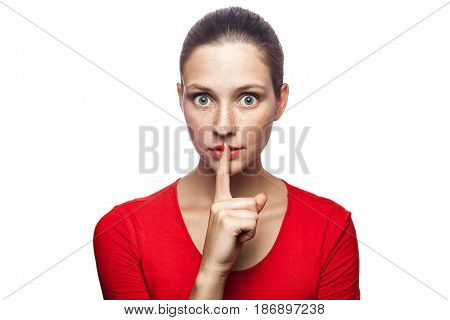 Portrait of serious woman in red t-shirt with freckles with shh sign on her lips. studio shot. isolated on white background.