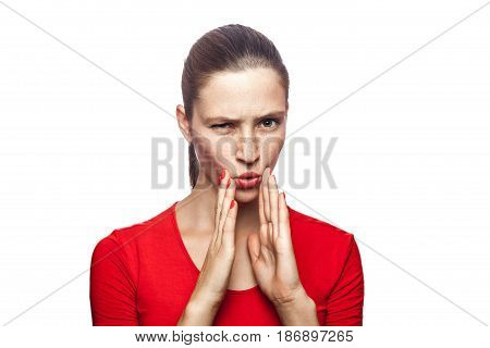 Portrait of serious woman in red t-shirt with freckles. looking at camera and telling secret studio shot. isolated on white background.