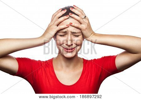 Portrait of sad unhappy crying woman in red t-shirt with freckles. closed eyes hands on head studio shot. isolated on white background.