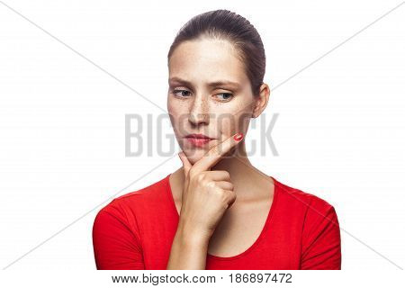 Portrait of thoughtful serious woman in red t-shirt with freckles studio shot. isolated on white background.