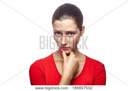 Portrait of thoughtful serious woman in red t-shirt with freckles studio shot looking at camera. isolated on white background.