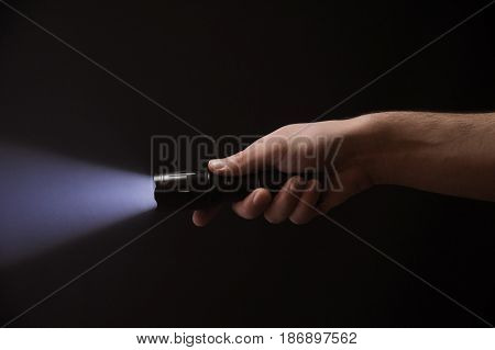 Black Flashlight In Male's Hand Isolated From Right Side Of The Frame On Black Background