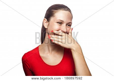 Portrait of happy laughter woman in red t-shirt with freckles with hand behind her mouth. studio shot. isolated on white background.