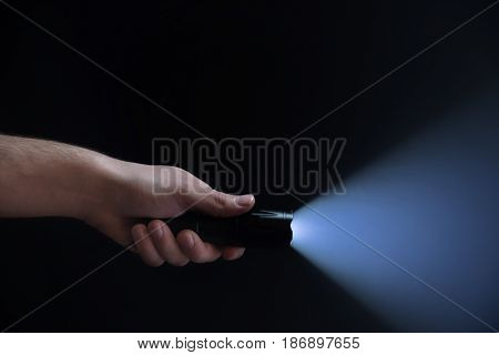 Black Flashlight With Wide Beam In Male's Hand Isolated From Right Side Of The Frame On Black Backgr