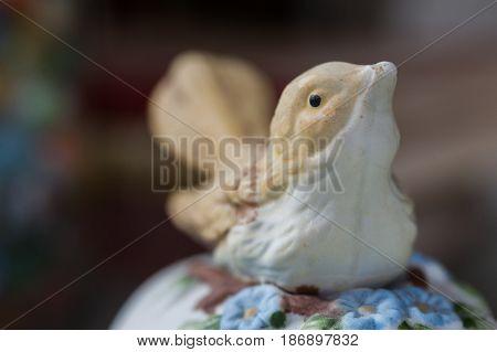 Macro detail of a bird porcelaine figurine on a ceramic jewlery box poster