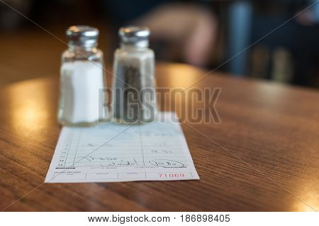 Salt and pepper shakers resting on top of the check