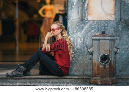 Young woman with blonde dreadlocks sitting on the street near the women's clothing store.