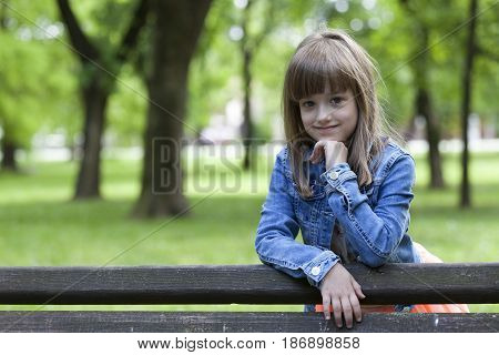 Portrait Of A Little Girl Standing Next To The Bench In The Park