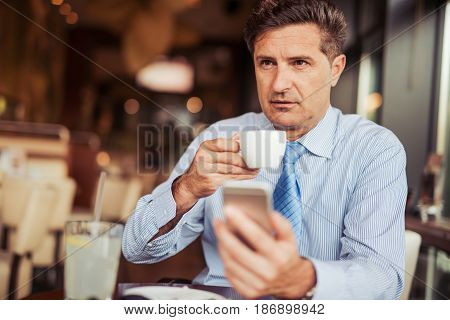 Attractive mid adult man drinking coffee in cafe and using his smart phone.