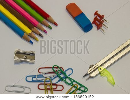 On a sheet of paper lie pencils, pencil sharpener, eraser, sticks and staples