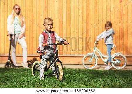 Woman with children on bicycles against wooden wall in afternoon in spring