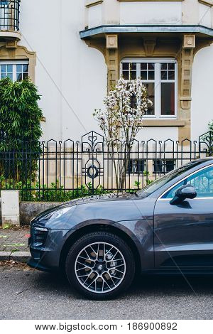 PARIS FRANCE - APR 2 2017: Cross section of side view of Porsche SUV parked on a French street with luxury real estate home in the background