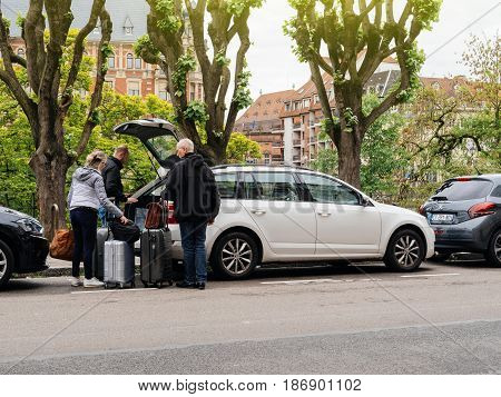 STRASBOURG FRANCE - MAY 7 2017: Group of seniors and adults loading luggage in Skoda Octavia estate car parked in European City