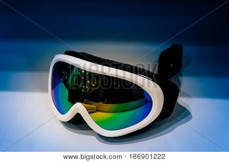 Modern ski googles on blue background in store table - ready
