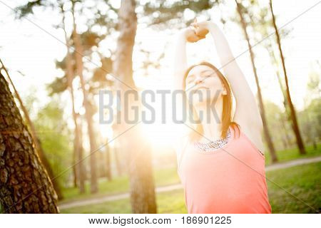 Young girl doing stretching exercises in park morning. Sunlight