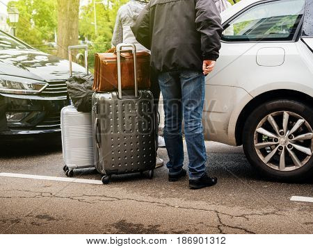 Low section of group of seniors and adults loading luggage in estate car parked city