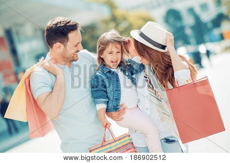 Happy family with little daughter and shopping bags in city.Saleconsumerism and people concept.