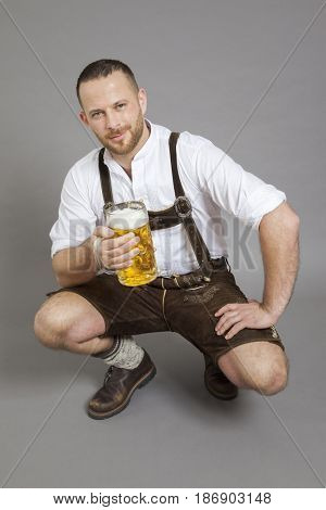 An image of a young bavarian kneeling with a beer