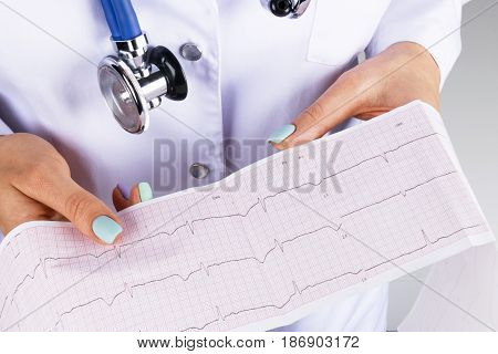 Electrocardiogram ecg in hand of a female doctor. Medical health care. Clinic cardiology heart rhythm and pulse test closeup. Cardiogram printout. poster