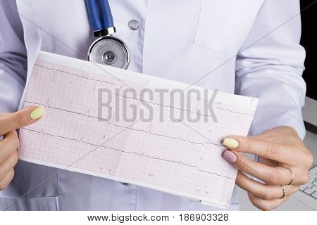 Electrocardiogram ecg in hand of a female doctor. Medical health care. Clinic cardiology heart rhythm and pulse test closeup. Cardiogram printout.