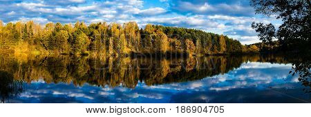 Autumn forest reflection of the lake under a bright sky