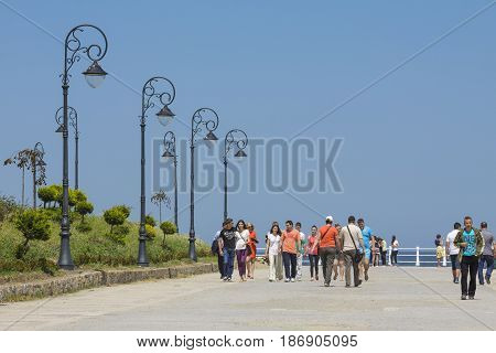 Constanta Romania - May 25 2014: Tourists enjoy the sights and stroll on Casino seafront promenade in Constanta the oldest living city in Romania founded around 600 BC on the Black Sea coast.