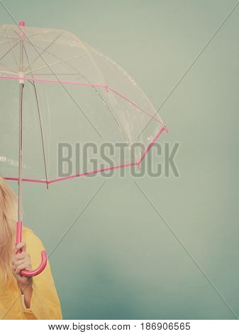 Rainy autumn day accessories ideas concept. Woman hand holding clear transparent umbrella