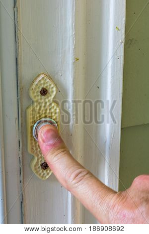 Male finger ringing a doorbell to a front door with a white frame on a green house