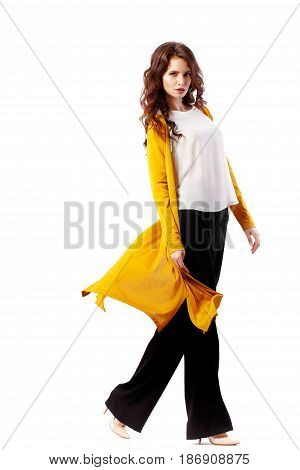 Fashion Model girl full length portrait isolated on white background. Beauty stylish brunette woman posing in yellow cardigan, white shirt, black pants in studio.